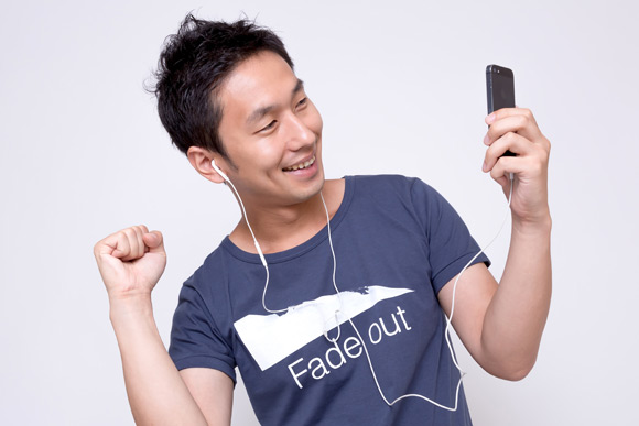 iPhone で音楽を聴いてノリノリな男性[モデル:大川竜弥]