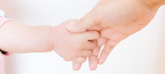 大人と子供の手。握力がなくなる病気に