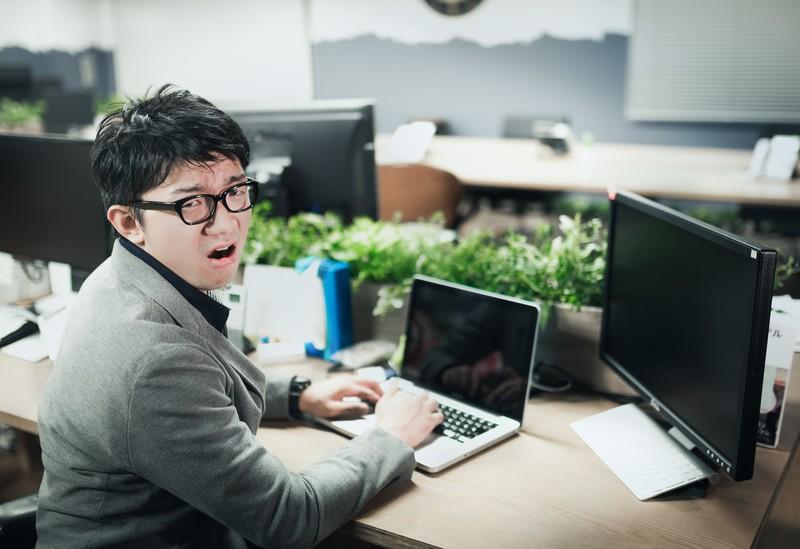 パソコンを触りながら、嘆く男性