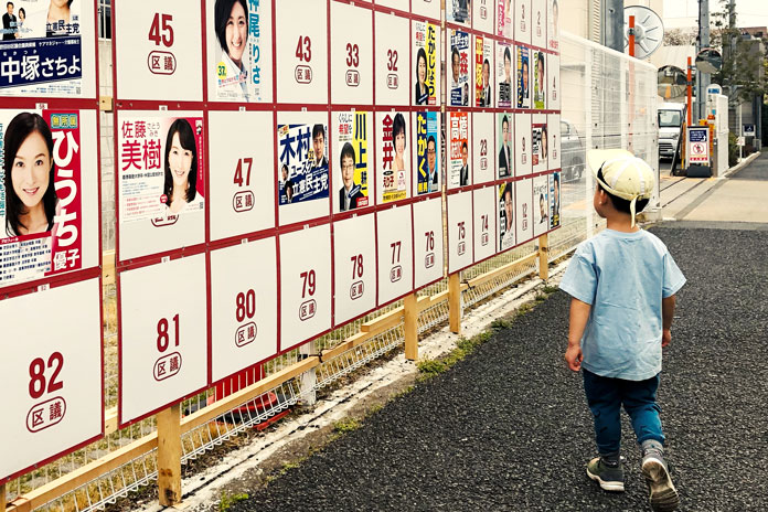 選挙ポスター掲示板を眺める区民